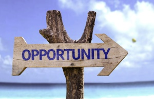 Opportunity wooden sign with a beach on background