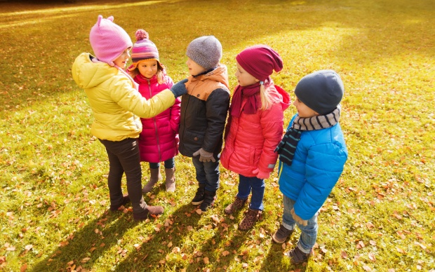 kids in autumn park counting and choosing leader