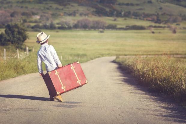 nio con maleta en la carretera